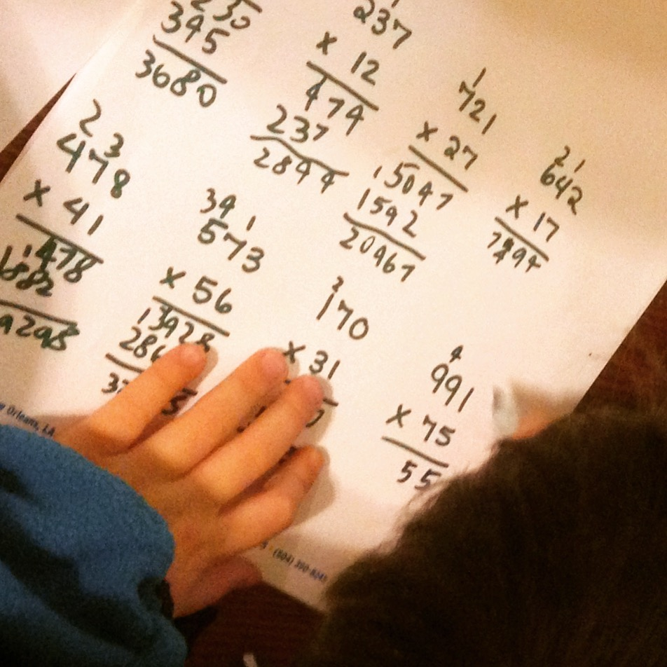 hands writing numbers and equations