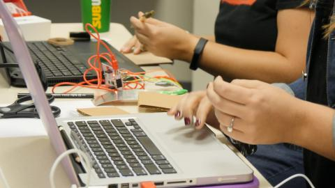 teachers' hands working on circuit boards and laptops